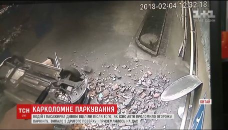 В Китае водитель и его пассажирка уцелели после падения автомобиля со второго этажа паркинга