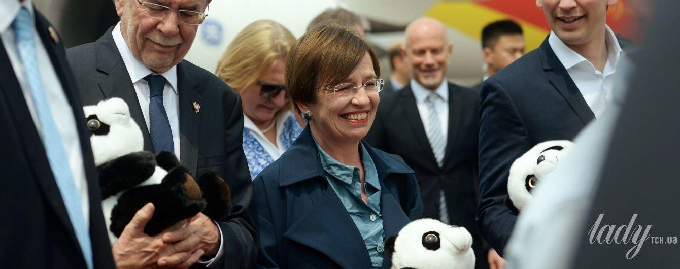 В темно-бирюзовой рубашке и с пандой в руках: первая леди Австрии в аэропорту