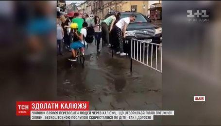 У Львові чоловік на велосипеді безкоштовно перевозив містян через величезну калюжу