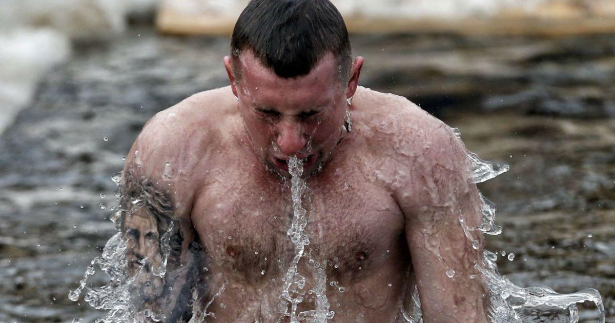 Чоловік купається в ополонці під час святкування Хрещення Господня (Водохреща) на Оболонській набережній у Києві. @ УНІАН