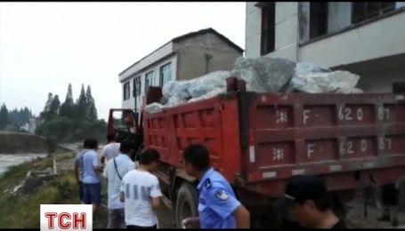 Десяток вантажівок з камінням скинули у річку, аби заблокувати дамбу у Китаї