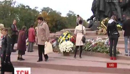 Люди впродовж цілого дня люди несуть квіти до пам'ятника жертва розстрілів