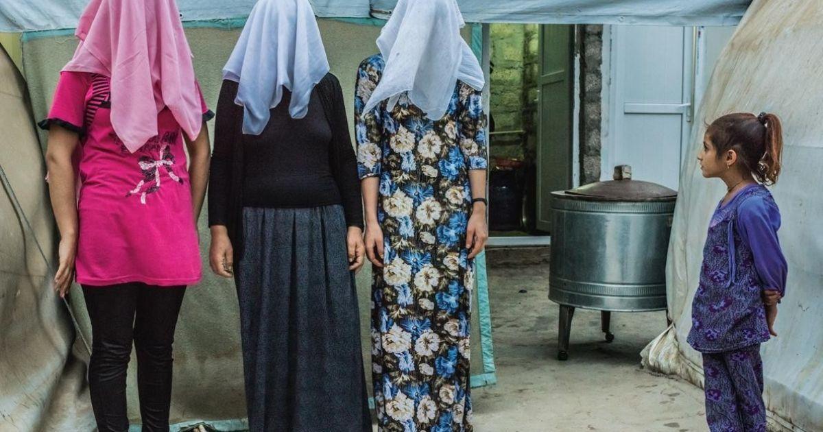 Дівчинка дивиться, як три курдські жінки фотографувалися зі своїми прихованими обличчями. Дві жінки кажуть, що вони були змушені вступити в шлюб з бійцями ІДІЛ, перш ніж втекти до табору біженців @ national geographic