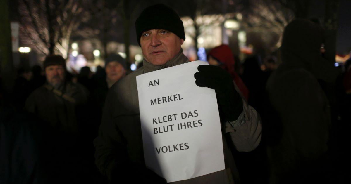 """Прихильник партії Альтернатива для Німеччини тримає плакат """"На руках Меркель кров її людей"""""""