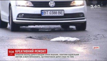 Українські інновації: у Дніпрі ями на дорогах вкрили мішками зі сміттям