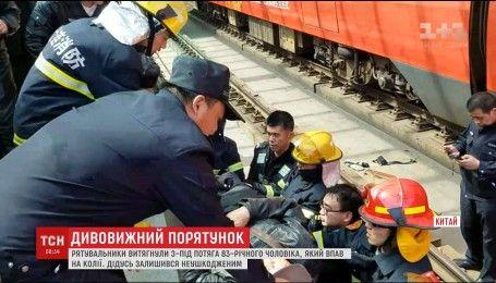 В Китае дедушка чудом спасся, упав под электричку
