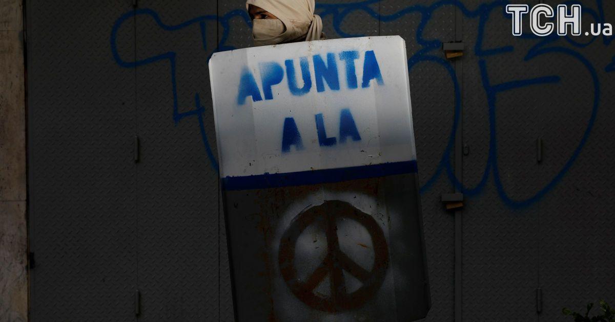 """Активіст тримає щит із написом """"Ціль на..."""" @ Reuters"""