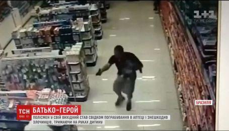 В Бразилии полицейский с ребенком на руках обезвредил двух грабителей, которые совершили нападение на аптеку