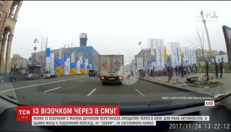 В Киеве мать с ребенком решила перейти Крещатик, несмотря на интенсивное автомобильное движение