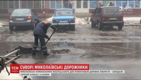 Николаевские коммунальщики ремонтировали дорогу, бросая горячий асфальт в лужу