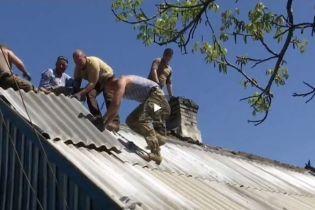 Ветерани АТО відзначили свято трударів, латаючи понівечену снарядом хату на Донбасі