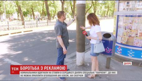 """У Дніпрі комунальники вдягли на стовпи спеціальні """"панчохи"""", аби боротися з рекламою"""