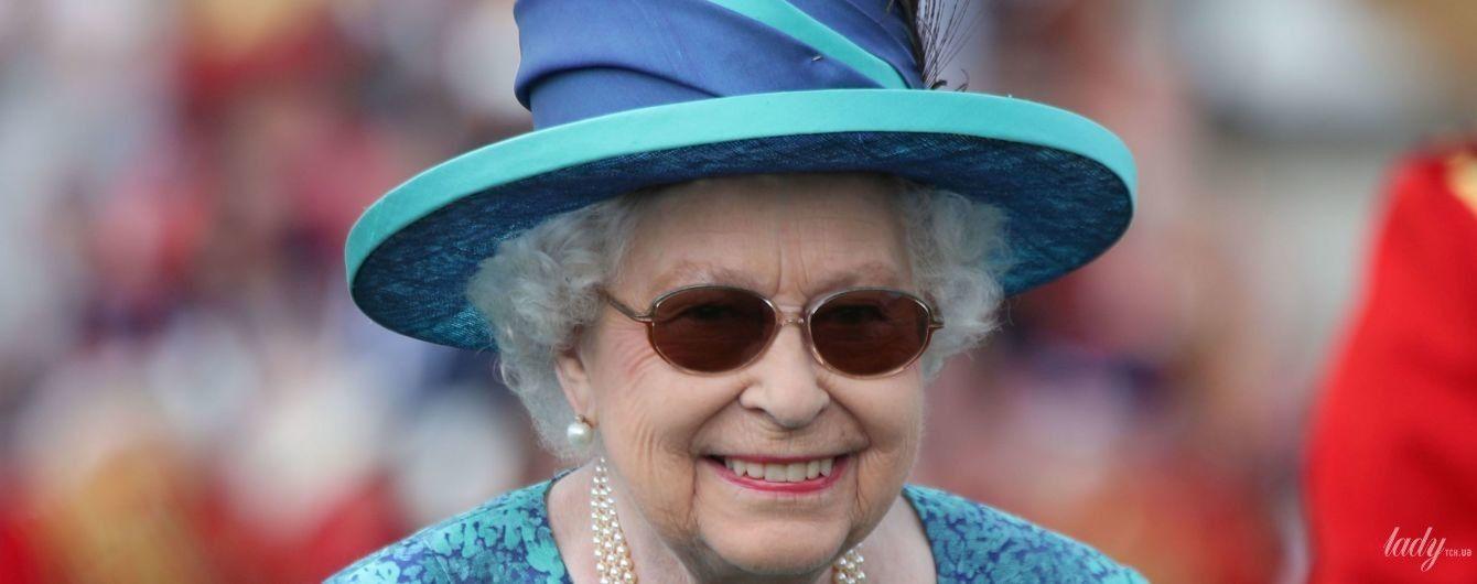 В солнцезащитных очках и шляпе с пером: королева Елизавета II в эффектном образе предстала на садовой вечеринке