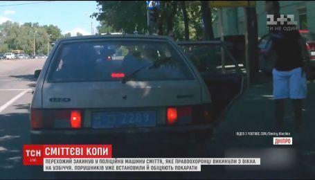В Днепре прохожий забросил в машину мусор, который из окна выбросили полицейские