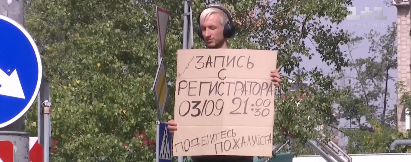 Киевлянин с плакатом возле дороги разыскивает видео с регистратора, которое помогло бы найти виновника ДТП