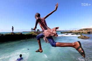 Будничная жизнь в Сомали: рыбаки носят рыбу на плечах, а дети купаются в океане одетыми