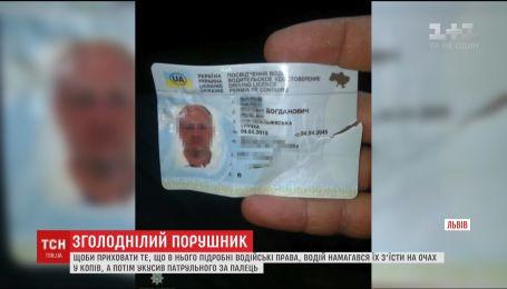 """Во Львове водитель """"БМВ"""" пытался проглотить водительское удостоверение и укусил копа за палец"""