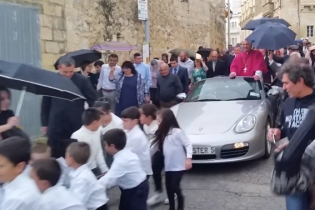 Сети возмущаются роликом, в котором десятки детей тянут священника в Porsche улицам Мальты