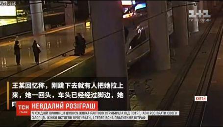 В Китае женщина внезапно прыгнула под поезд, чтобы разыграть своего парня