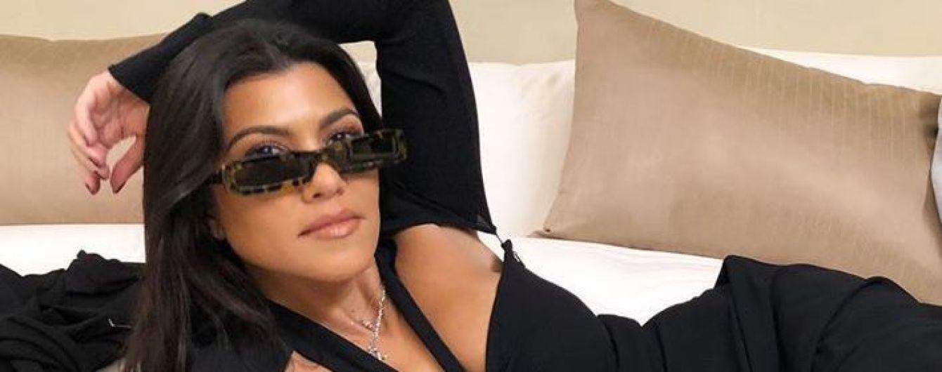 Кортні Кардашян у відвертій чорній сукні позувала на ліжку