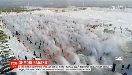 В Китае тысячи людей одновременно подбросили в воздух горячую воду, которая мгновенно превратилась в снег