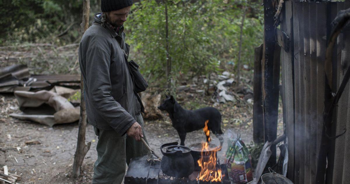 Мужчина готовит еду возле бомбоубежища @ Reuters