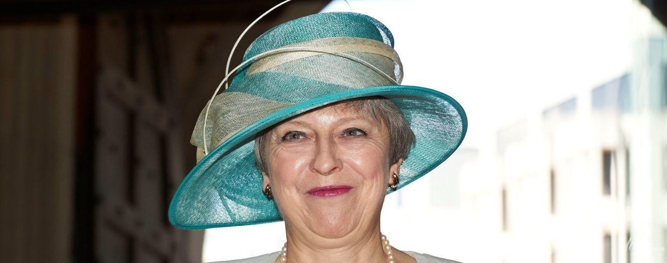 В платье с декольте и экстравагантной шляпе: элегантный образ Терезы Мэй