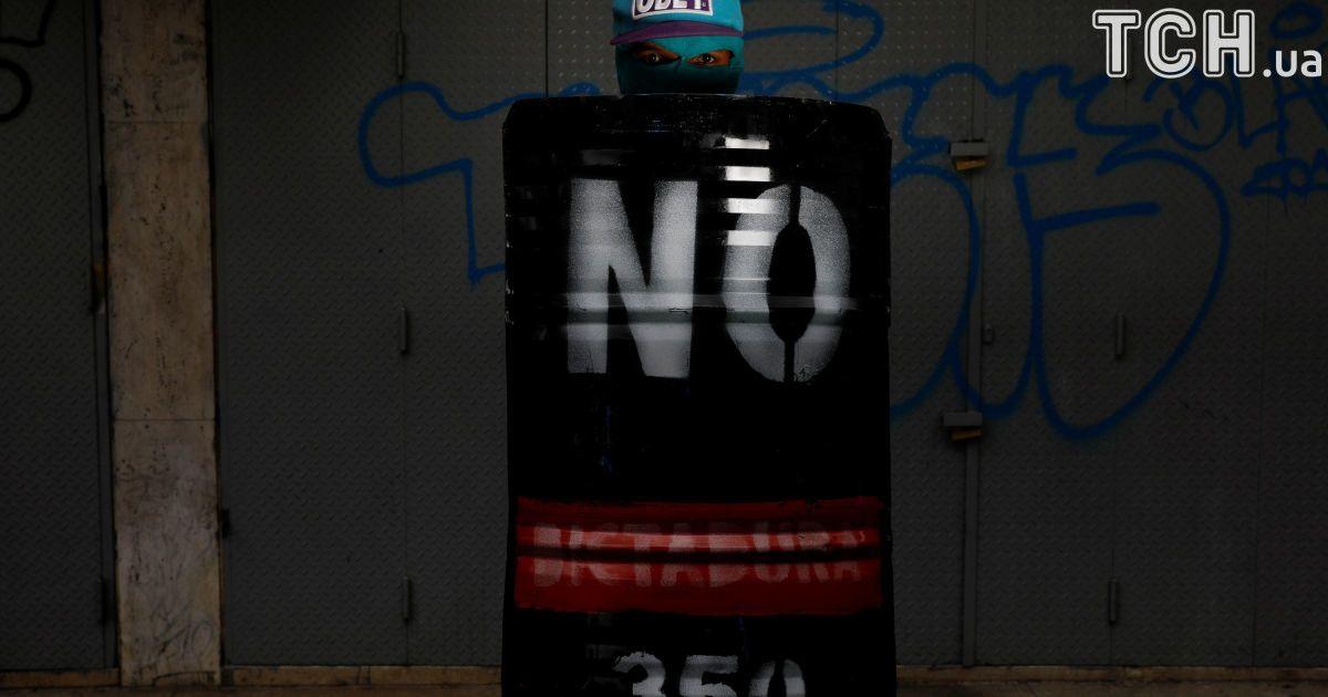 """Активіст тримає щит із написом """"Ні"""" @ Reuters"""