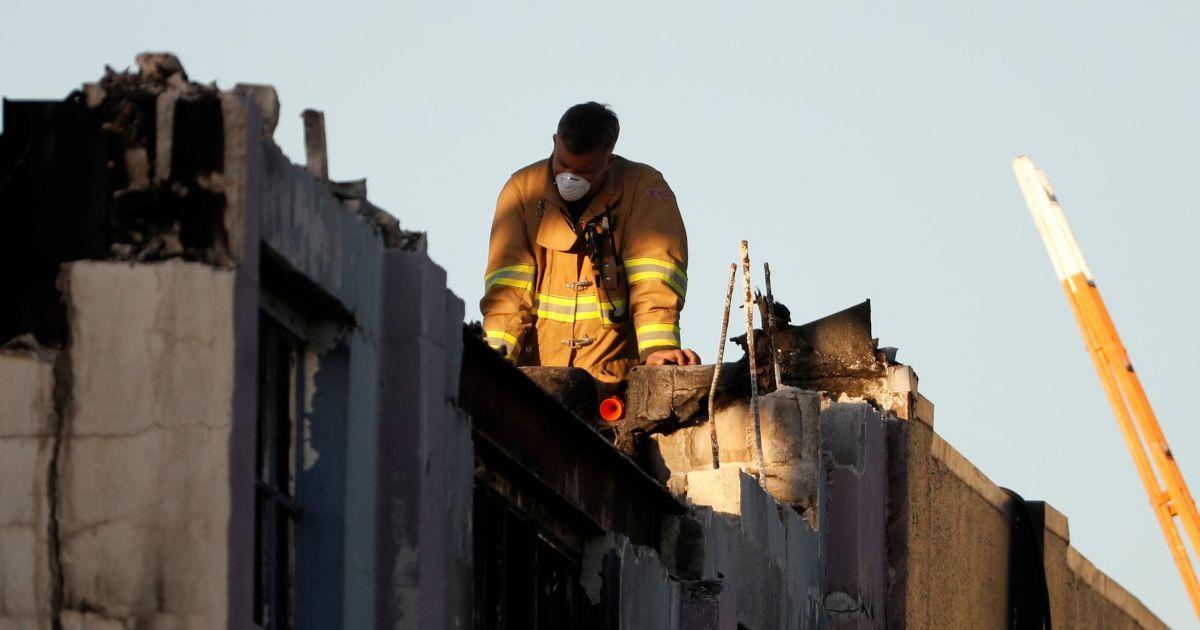 Рятувальник дивиться крізь дах на місці смертельної пожежі на складі в Окленді, штат Каліфорнія, від якої загинули більше 30 людей. @ Reuters