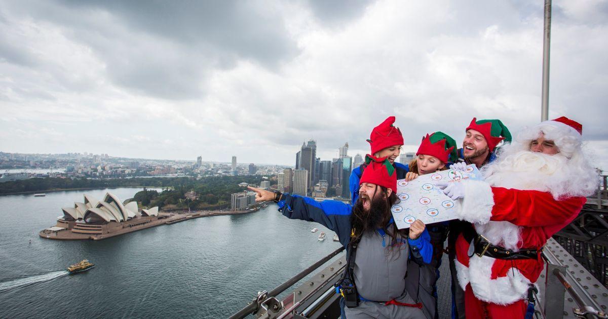 Люди, одягнені у Санта-Клаусів та його ельфів, стоять на вершині мосту Sydney Harbour Bridge із картою, на якій зображені австралійські будинки, куди потрібно доставити подарунки на Різдво. @ Reuters