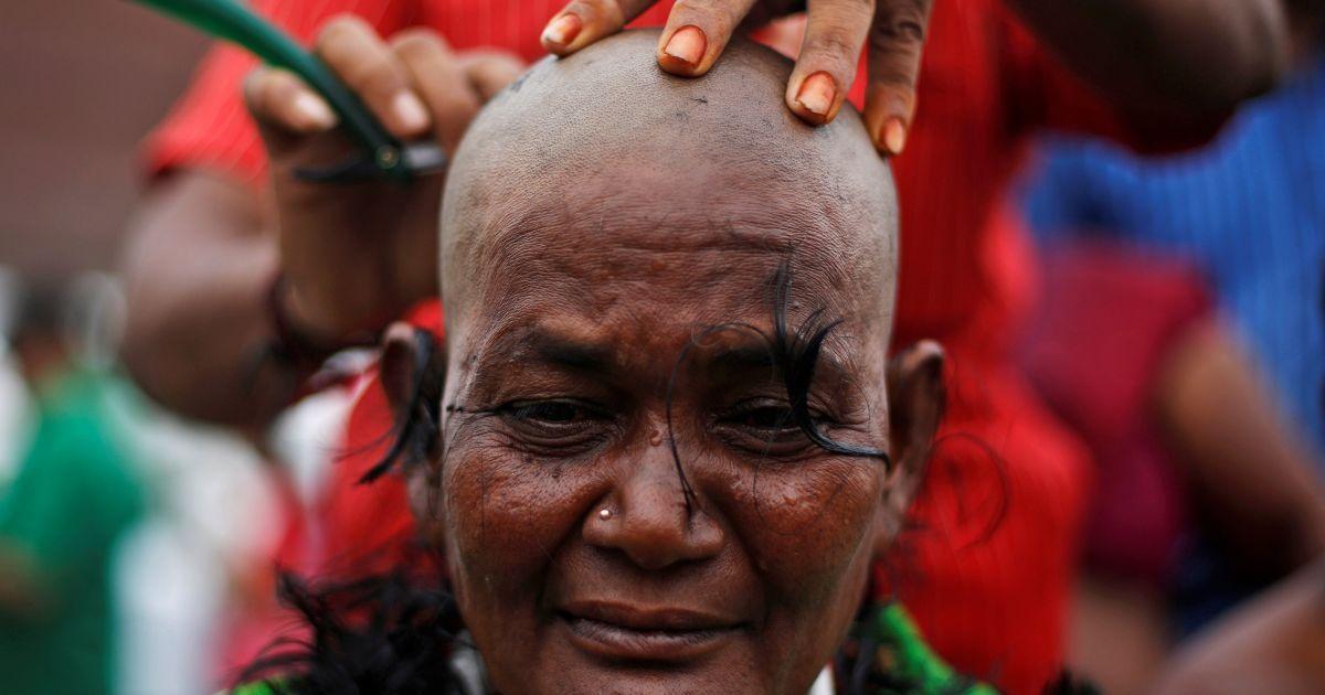 Прихильник прем'єр-міністра індійського штату Таміл Наду Джаярама Джаялаліта Джаярамана голить голову біля місця поховання політика у місті Ченнаї, Індія. @ Reuters