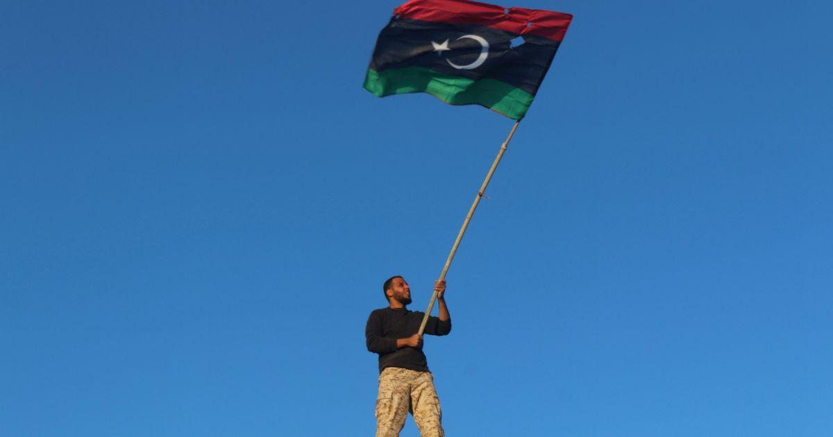 """Військовий лівійської урядової армії тримає прапор країни, святкуючи повне визволення міста Сирт, колишнього оплоту бойовиків """"Ісламської держави"""". @ Reuters"""