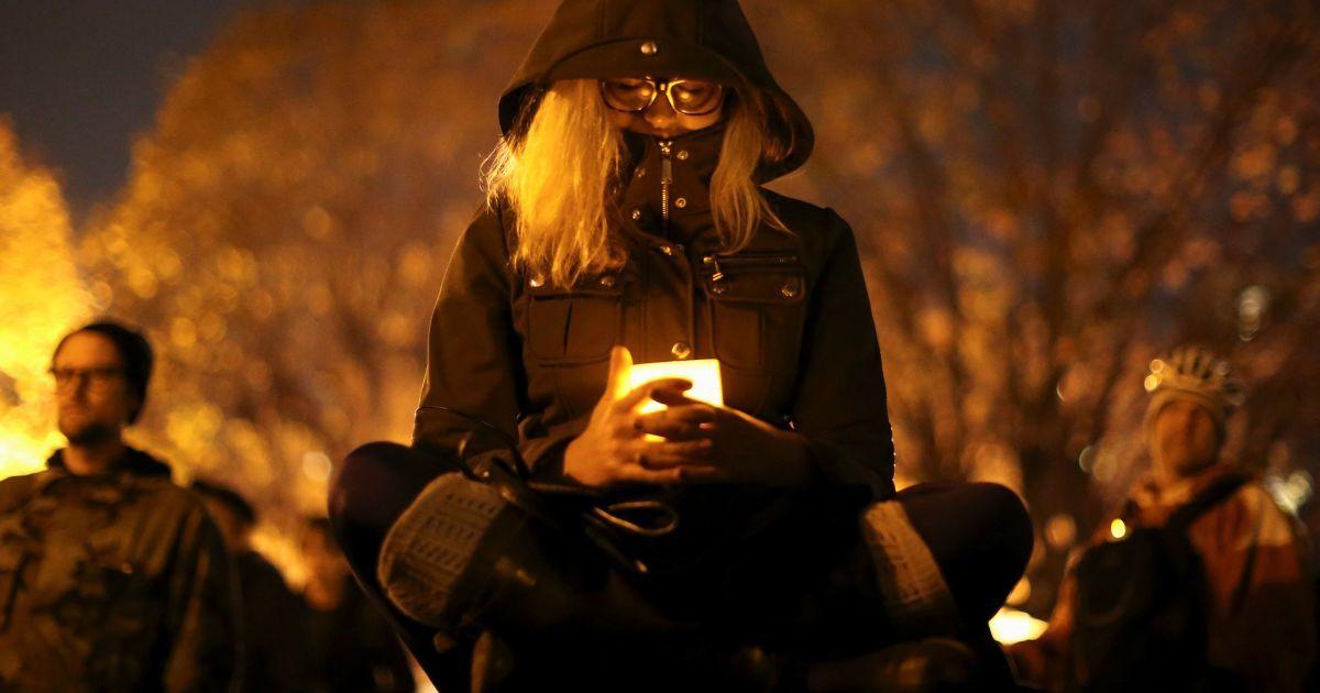 Жінка тримає свічку у пам'ять про жертв масштабної пожежі на складі в Окленді, штат Каліфорнія, яка забрала життя більше 30 людей. @ Reuters