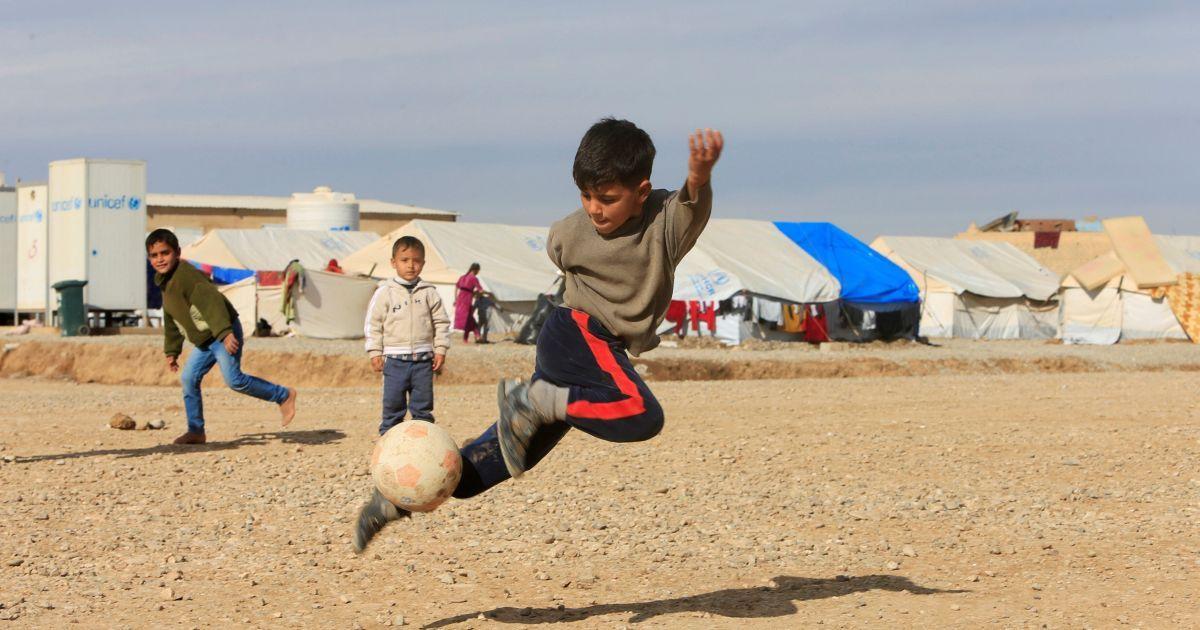 """Переміщені іракські діти, які втекли із захопленого бойовиками """"Ісламської держави"""" Мосула, грають у футбол у таборі Хазер в Іраку. @ Reuters"""