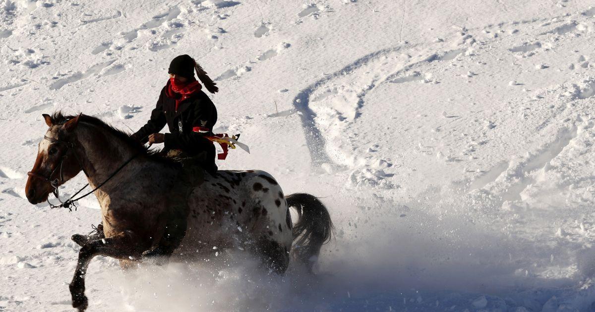 Молодий Індіанець їде на коні по снігу біля табору корінних мешканців Америки, які протестують проти планів прокласти трубопровід поруч із індіанською резервацією у Північній Дакоті. @ Reuters