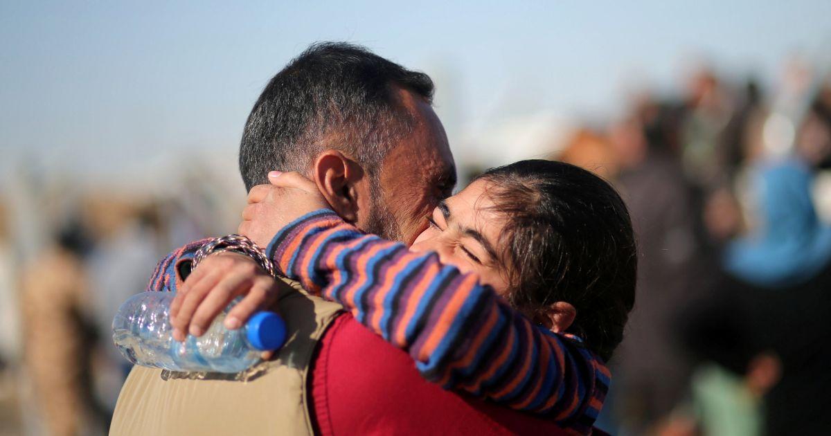 """Чоловік, який втік із захопленого бойовиками """"ІД"""" Мосула, обіймає свою доньку під час їхньої першої зустрічі після втечі з міста, після прибуття батька в табір Хазер, Ірак. @ Reuters"""