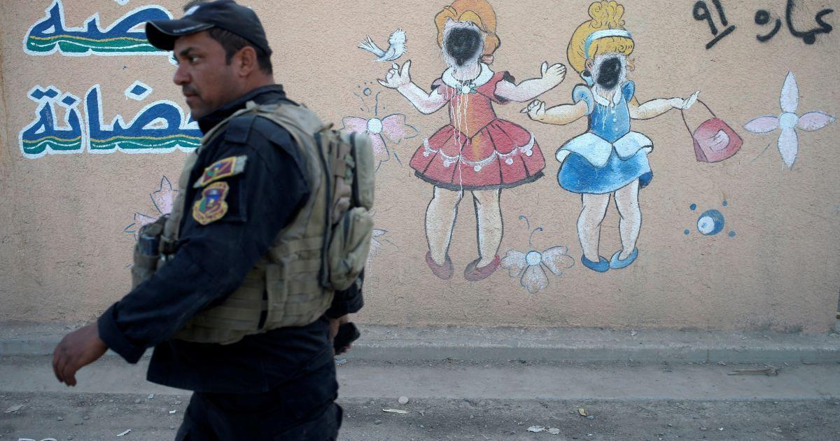 """Боєць іракського спецпризначення проходить повз мурал з намальованими дітьми, обличчя яких зафарбували бойовики """"ІД"""", на стіні дитячого садочка у Мосулі, Ірак. @ Reuters"""