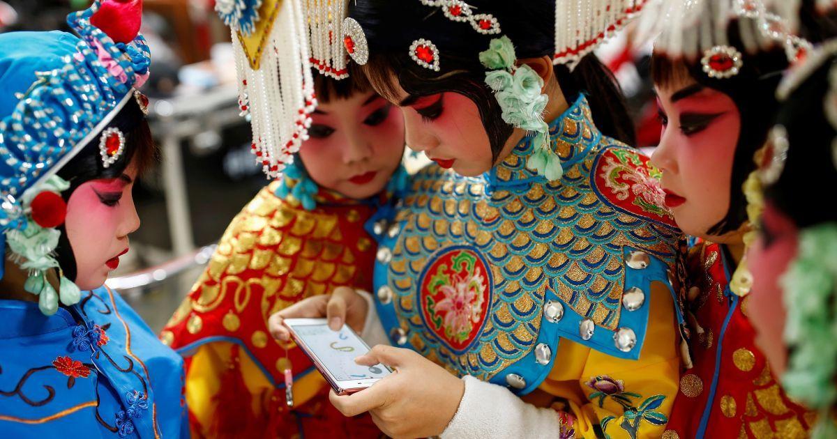 Учасниця групи артистів традиційної китайської опери грає в гру на своєму телефоні, а інші спостерігають за нею, під час антракту у Національній академії китайського театрального мистецтва в Пекіні, Китай. @ Reuters