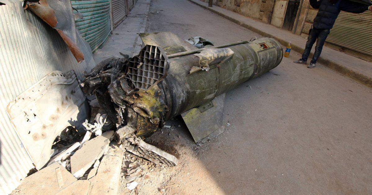 Человек осматривает ракету, которая не разорвалась, удерживаемого повстанцами в районе Аль-Квартеджи в Алеппо, Сирия. @ Reuters