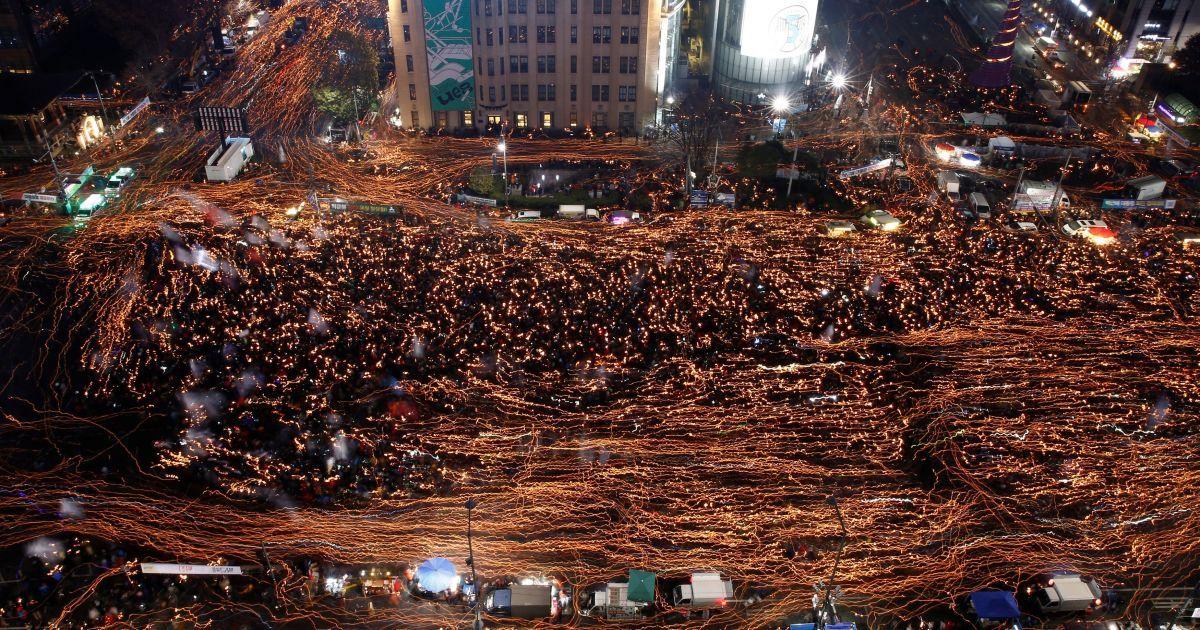 Місцеві жителі тримають свічки під час мітингу проти підозрюваної у корупції президента Південної Кореї Пак Кин Хе на головній вулиці в Сеулі, Південна Корея. На акцію протесту вийшли 1,3 млн людей. @ Reuters