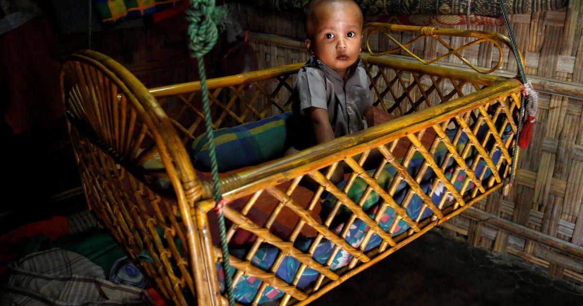Дитина реагує на камеру, сидячи у колисці у незареєстрованому таборі біженців у Кокс Базар, Бангладеш. @ Reuters