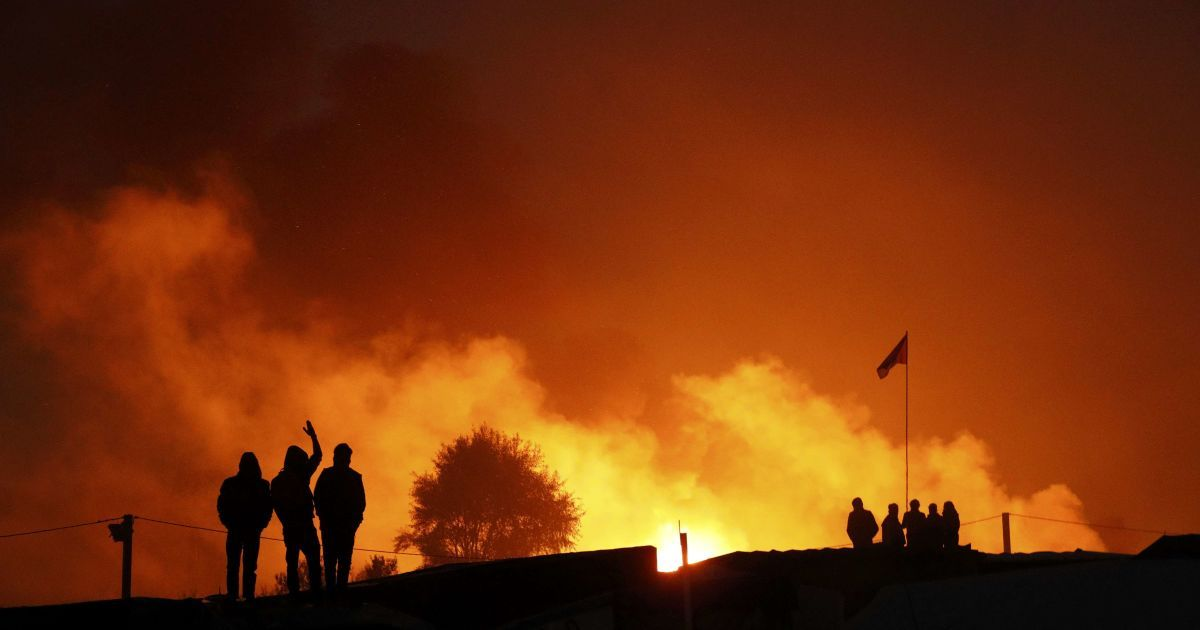Мігранти збираються біля вогню на другий день їх евакуації в прийомні центри у Франції, в рамках демонтажу табору під назвою «Джунглі» в Кале. @ Reuters