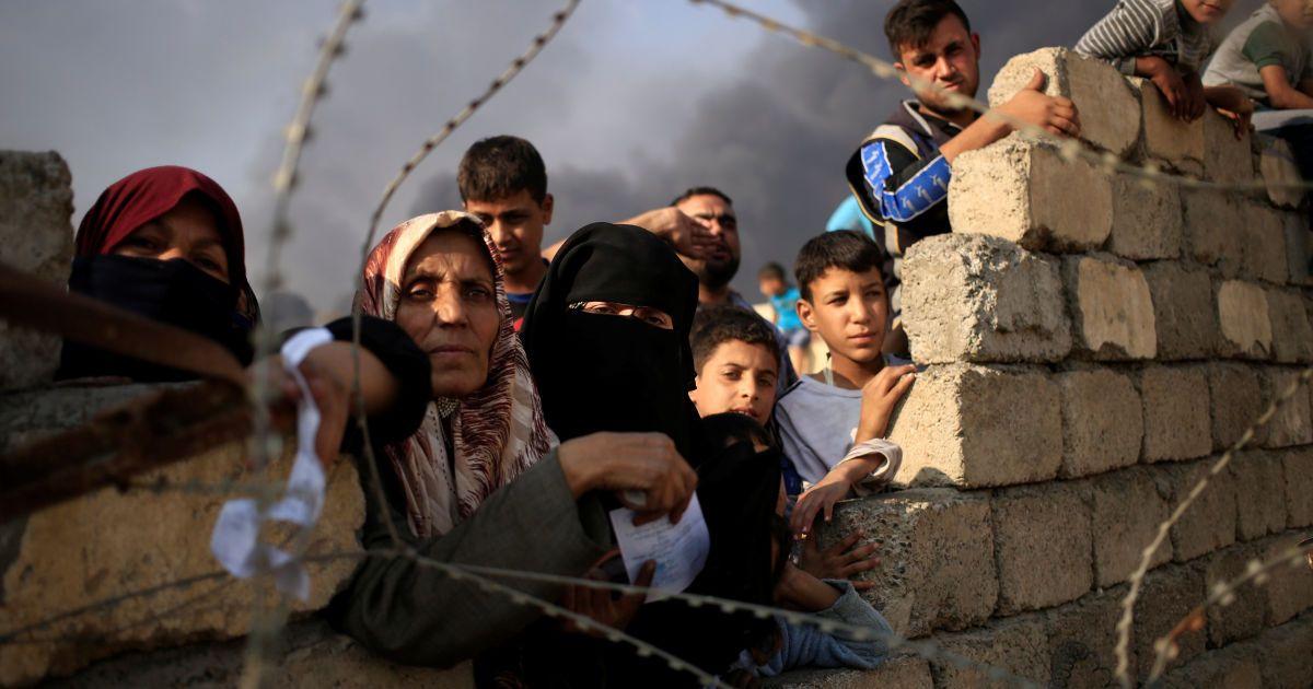 Переміщені люди чекають на гуманітарну допомогу за межами центру обробки в Кайара на південь від Мосула, Ірак. @ Reuters