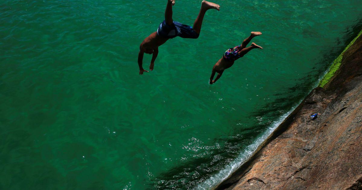 Чоловіки стрибають в море на пляжі Лемі в Ріо-де-Жанейро, Бразилія. @ Reuters