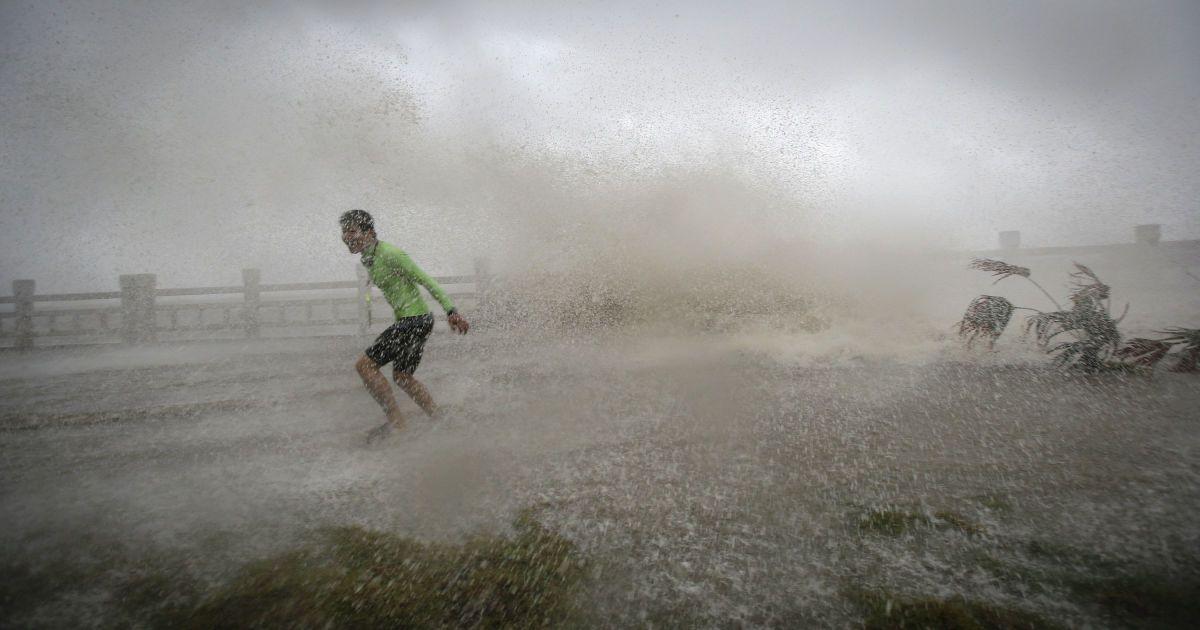 Чоловік тікає від хвилі на пляжі під час тайфуну Саріка у провінції Хайнань, Китай. @ Reuters