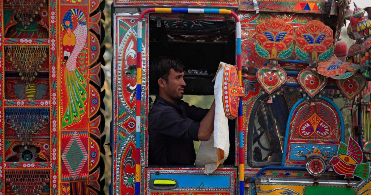 Водій вантажівки очищає дзеркало своєї прикрашеної вантажівки, Пакистан. @ Reuters