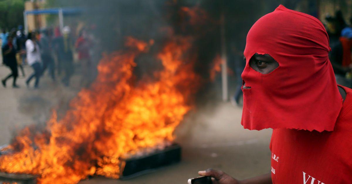Протестувальник стоїть перед барикадою під час акції протесту з вимогою безкоштовної освіти у технологічному університеті Ваал у Південній Африці @ Reuters