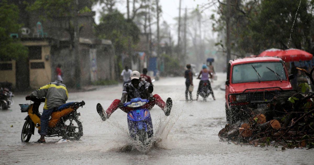 Людина на мотоциклі їде по затопленій вулиці під час дощу після урагану Метью в Ле-Ке, Гаїті. @ Reuters
