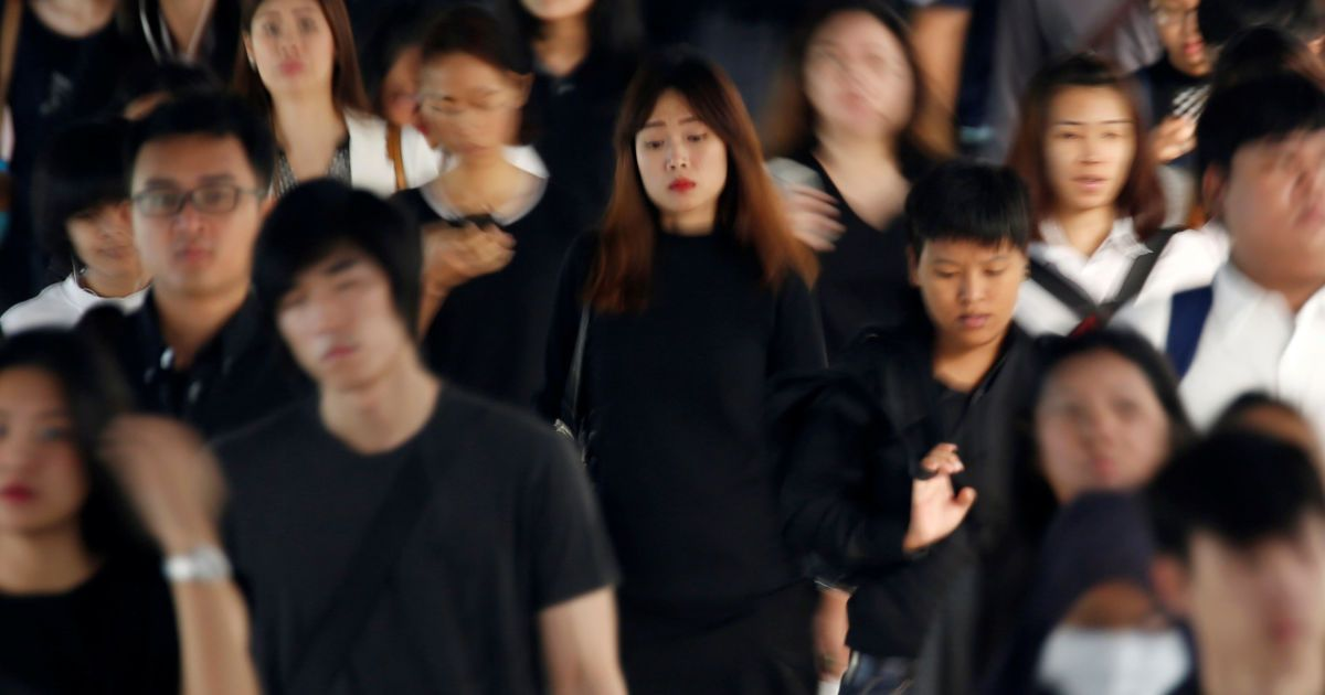 Пасажири, одягнені в чорно-білий або чорний одяг у знак скорботи за королем Таїланду Пуміпоном Адульядетом, йдуть під час ранкової години пік на вокзалі у Бангкоку, Таїланд. @ Reuters