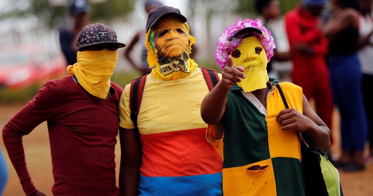 Протестувальники у масках жестикулюють у бік фотографа під час акції протесту з вимогою безкоштовної вищої освіти у Північно-Західному університеті у місті Вандербійлпарк, Південна Африка. @ Reuters